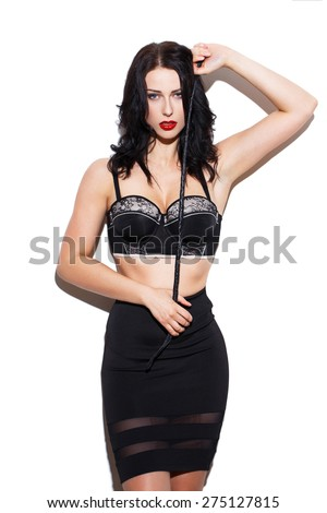 Sexy brunette woman holding whip at white wall - stock photo