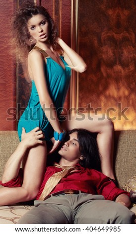 Sexy brunette woman in a blue dress and attractive hot man enjoying on a sofa in a luxury room.