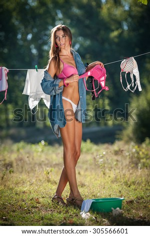 Sexy brunette woman in bikini and shirt putting clothes to dry in sun. Sensual young female with long legs putting out the washing to dry in sunny day. Perfect body housewife, outdoor shot in forest - stock photo
