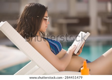 Sexy brunette woman in bikini relaxing near swimming pool on tropic island in hot weather on the seaside reading a book.Woman relaxing in deck chair.Sunscreen,protection,summer body,summer recreation - stock photo