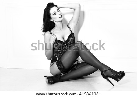 Sexy brunette woman in black underwear sit on floor, black and white