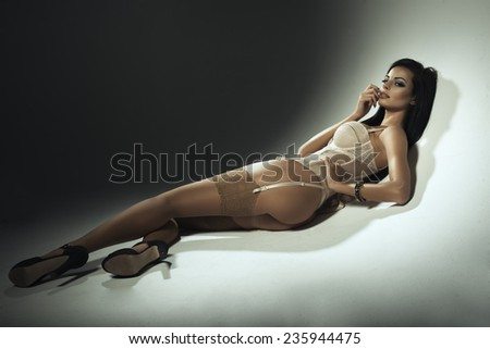 Sexy brunette woman in lingerie lying on floor - stock photo