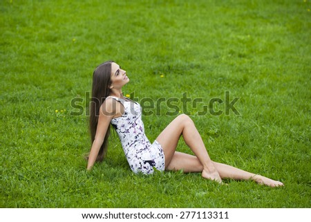 Sexy brunette woman in short dress sitting on green grass - stock photo