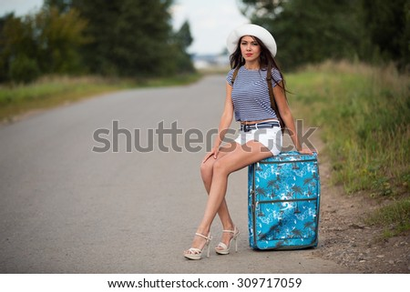 sexy brunette woman in shorts , t-shirt and white hat sitting on bag hitch hiking on road
