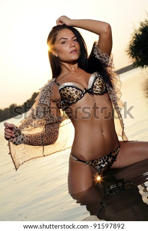 Sexy brunette woman in water at sunset .Erotic art photo.
