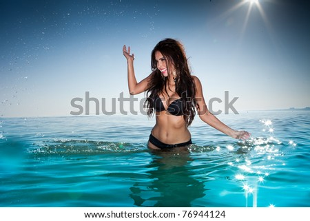 sexy brunette woman in water wearing bikini