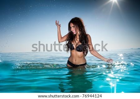 sexy brunette woman in water wearing bikini - stock photo