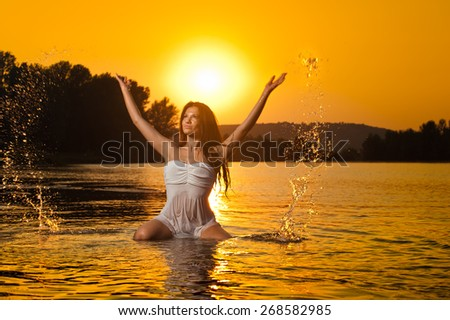 Sexy brunette woman in wet white lingerie posing in river water with sunset on background. Young female at the beach in twilight scenery. Attractive girl in summer evening over dramatic sky. - stock photo