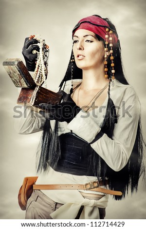 Sexy brunette woman pirate  opens the treasure chest - stock photo