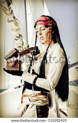Sexy brunette woman pirate with a gun opens the treasure chest - stock photo