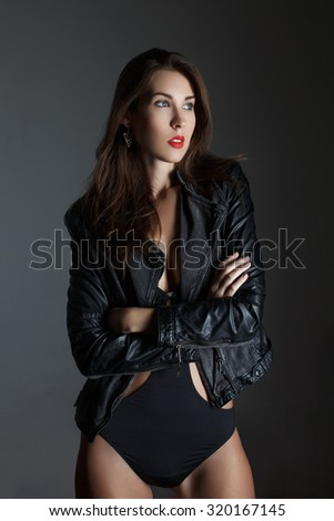 Sexy brunette woman posing at night on grey background - stock photo