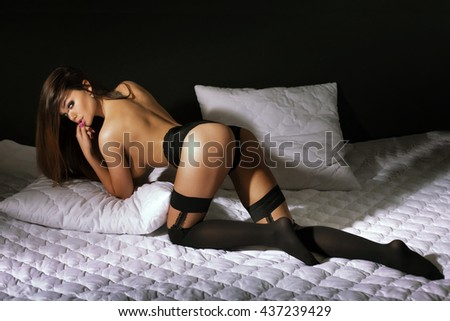 Sexy brunette woman posing in bed, wearing sensual black lingerie and stockings. Girl with perfect slim body.  - stock photo