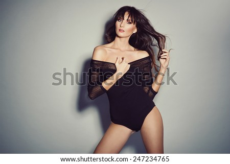 Sexy brunette woman posing in black bodysuit