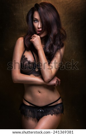 Sexy brunette woman posing in elegant lingerie, looking at camera. Girl with perfect body. - stock photo