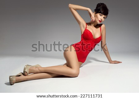 sexy brunette woman posing in red lingerie - stock photo