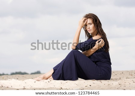 Sexy brunette woman posing in violet dress. - stock photo