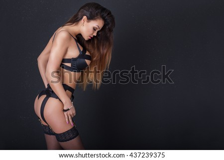 Sexy brunette woman posing, wearing sensual black lingerie and stockings. Girl with perfect slim body. - stock photo