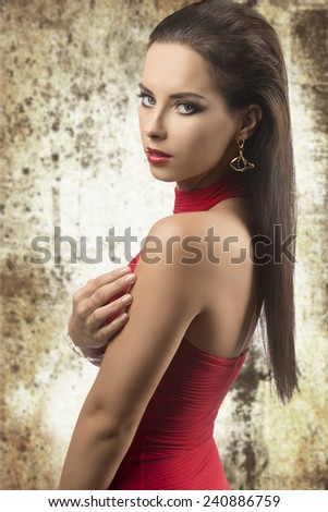 sexy brunette woman posing with long smooth hair, golden jewellery and red stylish dress. Looking in camera with sensual expression and naked shoulders   - stock photo