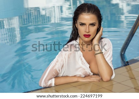 Sexy brunette woman relaxing in swimming pool, looking at camera. Beauty portrait. - stock photo