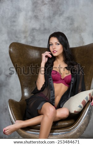 Sexy brunette woman sitting on modern chair - stock photo
