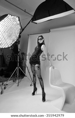 Sexy brunette woman wearing back minidress and mask  on isolated white studio background with white S shape plastic chair and lightstands and softboxes - stock photo
