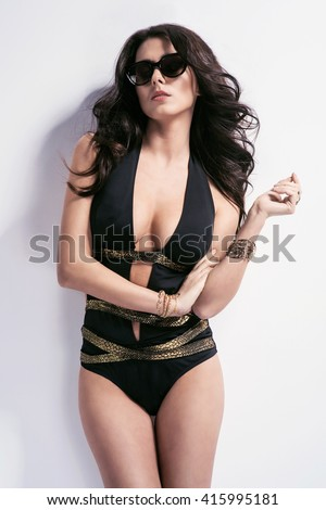 Sexy brunette woman wearing black swimwear with sunglasses posing on white background. Perfect body, wide cleavage, accessories - stock photo