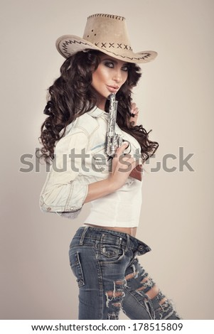 Sexy brunette woman with amazing hair in hat. Beautiful cowgirl in studio. - stock photo