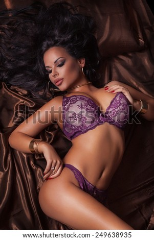 Sexy brunette woman with perfect body posing in lingerie lying in bed. - stock photo