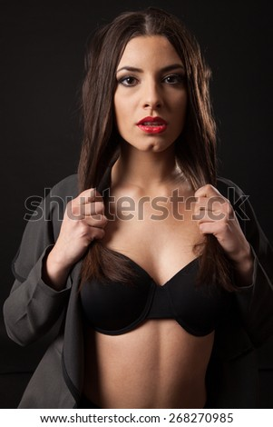 Sexy brunette woman with retro black lingerie. Black background.  - stock photo