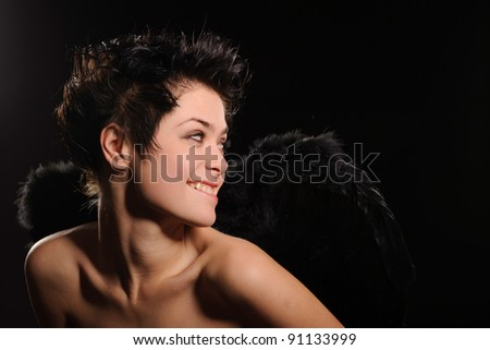 Sexy brunette woman with wings, isolated on black - stock photo