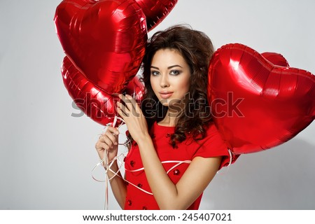 sexy brunette young woman in red dress with a heart-shaped balloons. Valentine's day - stock photo