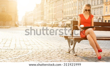 Sexy Business Woman using digital tablet. Beautiful woman in red high-heeled shoes and dress enjoying sunny morning in the city, browsing Internet and drinking coffee. - stock photo