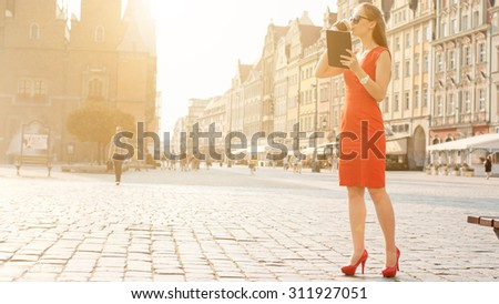 Sexy Business Woman using digital tablet. Slow Motion. Beautiful woman in red high-heeled shoes and dress enjoying sunny morning in the city, browsing Internet and drinking coffee. Lens Flare.