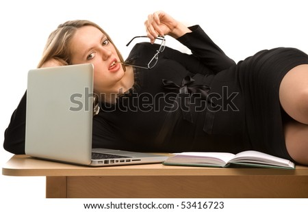 Sexy businesswoman lying on the desk and holding the rim of an eye-glass in her mouth - stock photo