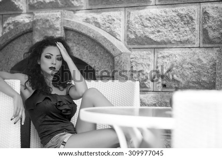 Sexy busty pretty brunette girl with curly hair and bright makeup in summer clothes sitting in cafe in chair at table with vase of fresh marigold flowers black and white copyspace, horizontal picture - stock photo