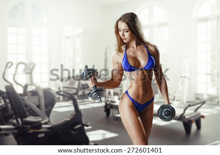 sexy busty young woman in a bikini workout training with dumbbells in gym - stock photo