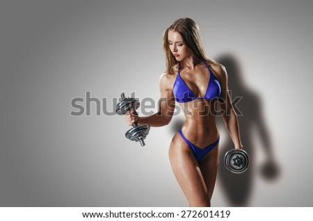 sexy busty young woman in a bikini workout training with dumbbells isolated studio portrait - stock photo