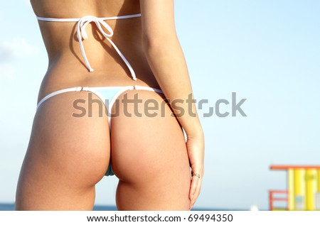 Sexy butt in thong bikini on female bikini model