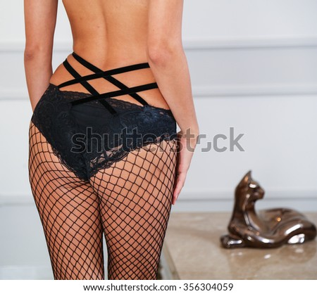 Sexy buttocks of a woman wearing black fishnet tights, interior background. Closeup view. - stock photo