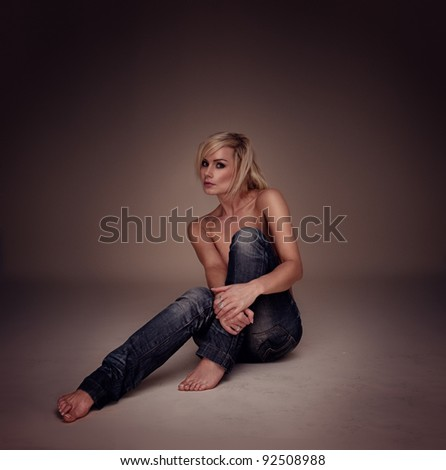 Sexy Casual Blonde Woman seated on the floor implied topless, studio portrait highligted on brown - stock photo