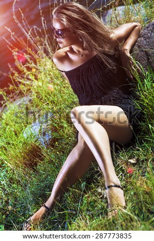 Sexy Caucasian Blond Female Model In Sunglasses Posing Outdoors Sitting On Grass.Vertical Image Composition - stock photo