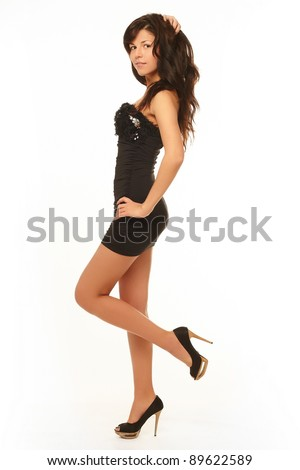 Sexy Caucasian brunette lady in black dress isolated on white background full length without makeup - stock photo