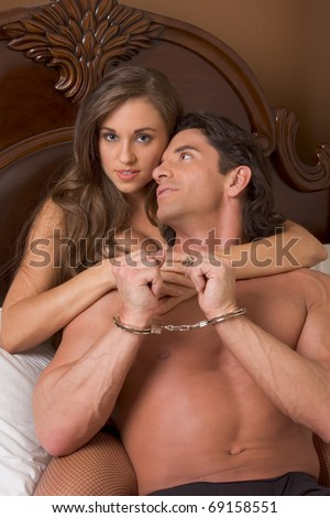 Sexy Caucasian couple in love sexual games, man in handcuffs - stock photo