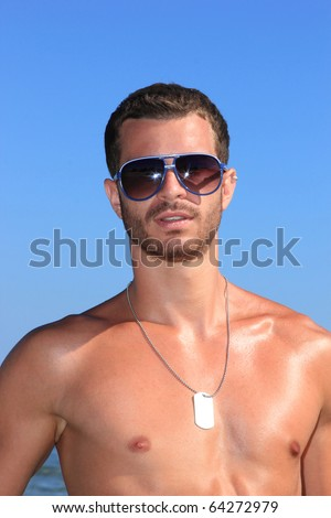 sexy caucasian fit man posing at the  beach - stock photo