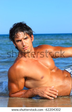 sexy caucasian fit man posing in a beach in Greece - stock photo