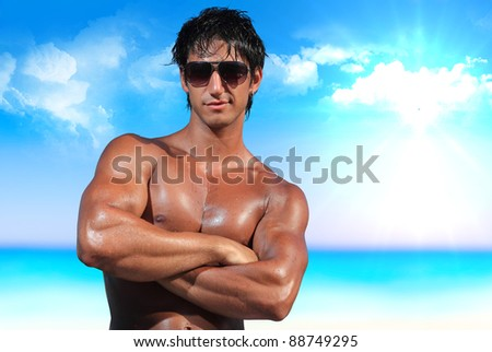 sexy caucasian fit man posing on the beach - stock photo