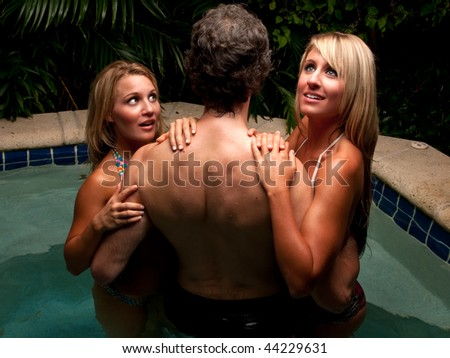 Sexy caucasian girls flirting with young man in a jacuzzi. - stock photo