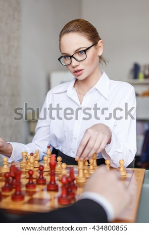 Sexy ceo playing chess with business partner in office - stock photo