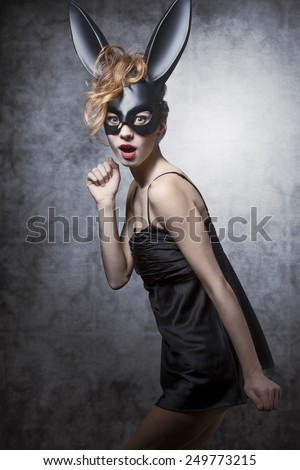 Sexy, charming, elegant, lovely woman in carnival dress and bunny mask. She has got curly wild hair and nice makeup. - stock photo