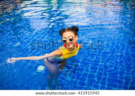Sexy cheeky, sassy, beautiful, happy tanned cool hipster girl with perfect body swimming in the pool fashion accessories, yellow top, mini bikini, fashionable hairstyle, Sportive style, trendy outfit
